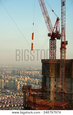 Two Construction Cranes Above A Congested City