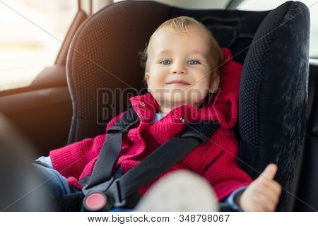 Cute Caucasian Toodler Boy Sitting In Child Safety Seat In Car During Road Trip. Adorable Baby Smili