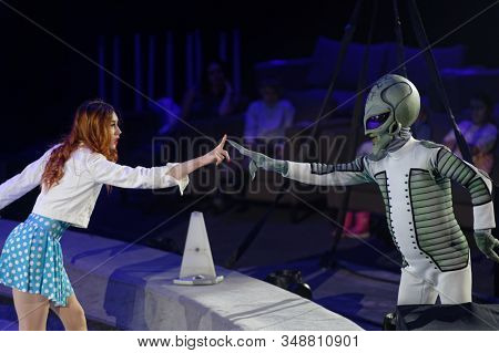 ST. PETERSBURG, RUSSIA - DECEMBER 27, 2019: Circus actors showing the contact with an extraterranean on the circus arena during the premiere of the show OFU. Landing in Saint-Petersburg
