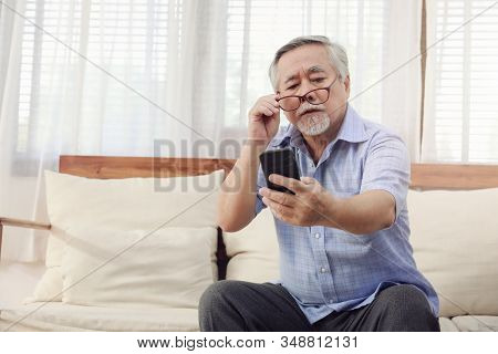 Older Men Move Glasses Down To Look At The Phone In The Hand Due To Long Sighted Problems, Which Mak