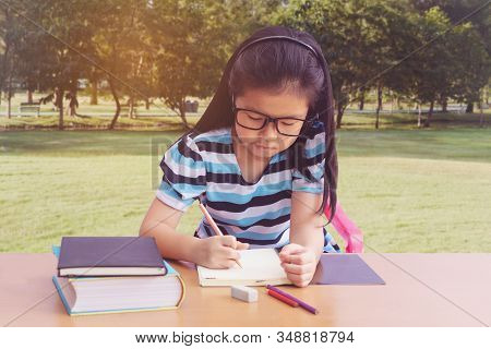 Asian Little Girl Writeing A Book On Table. Graden Background