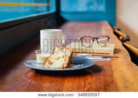 Fruit Cake With Coffee Mug On A Wooden Table In Cafe.