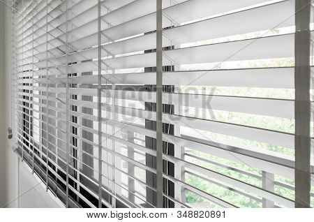 Closeup White Color Wooden Blind With White Ladder Tape Curtains.sunlight Through The Windows In The