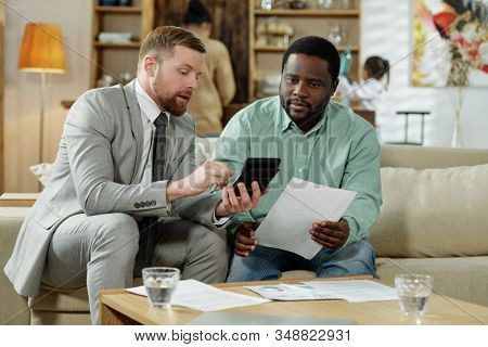 Adult black man with professional adviser sitting on couch with calculating machine discussing real estate mortgage