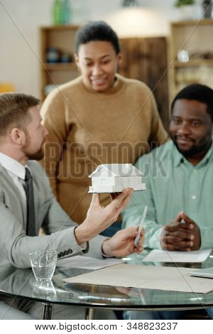 Elegant man with house model advising black couple on real estate purchase gathering at table