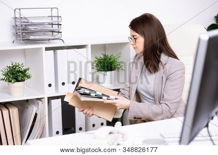 Busy young woman in glasses sitting at desk and examining notes in organizer while working with files in office