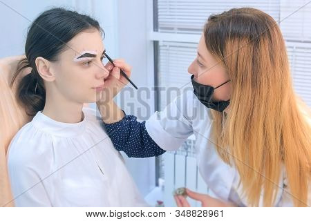 Cosmetologist Is Tinting Woman Eyebrows With Brown Paint In Beauty Clinic. Beautician Applying Natur