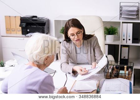 Young social worker in glasses talking to senior woman and pointing at document while assisting client in receiving services in person