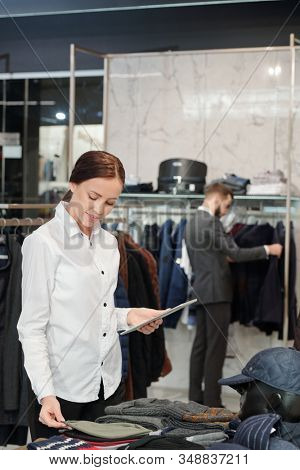 Content young female clothing store employee in white shirt using tablet while checking display of garments in shop