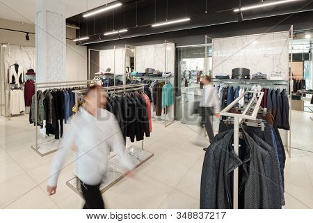 Blurred motion of sales consultants in clothing store with racks and accessories on shelves