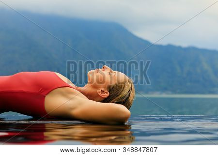 Young Woman Relax In Infinity Pool With Lake View. Natural Hot Spring Spa Under Batur Volcano. Trave