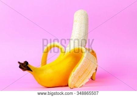 An Open Banana Symbolizing The Male Sexual Organ In An Erect State. Pink Background. Concept Of Pote