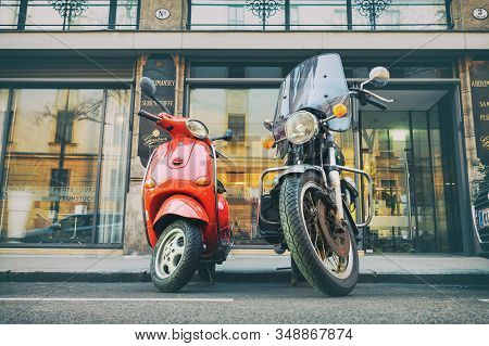 Vienna - January 12th, 2020: Vintage Red Vespa Scooter And Black Cycle Parked Onempty Italian City S