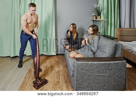 A Muscular Man Is Tidying Up The Room With Vacuum Cleaner. Two Young Women Watch As An Athletic Male