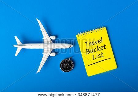 Travel Bucket List On Blue Background With Compas And Toy Airplane. Trip Travel Destination And Most