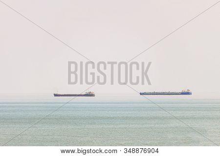 Two Freight Ship In Sea On Heat Hazy Horizon