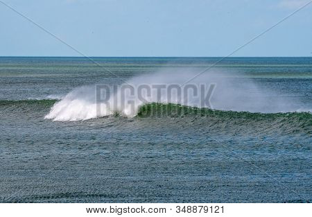 Wind Blows Spray From A Wave On The Atlantic Ocean.