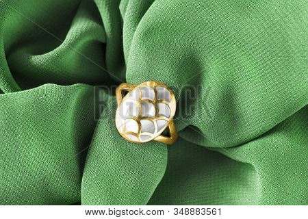 Gold Nacre Ring On Green Draped Silk Background Closeup