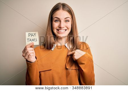 Young beautiful blonde woman holding pay taxes to goverment reminder over yellow background with surprise face pointing finger to himself