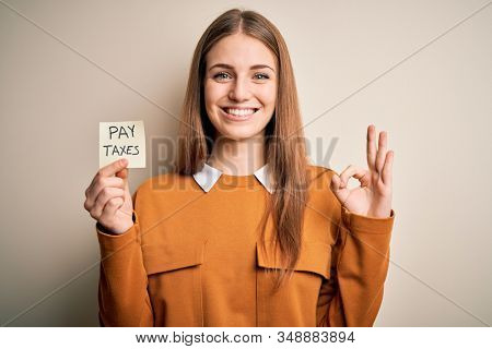 Young beautiful blonde woman holding pay taxes to goverment reminder over yellow background doing ok sign with fingers, excellent symbol