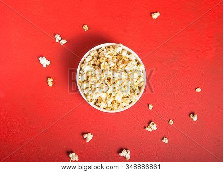 Popcorn Viewed From Above On Red Background. Child Eating Popcorn. Human Hand.  Cinema Snack Concept