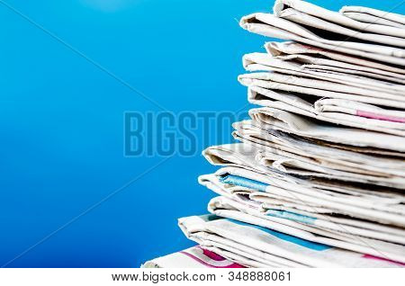 Newspapers Folded And Stacked On The Table With Blue Background.closeup Stack Newspaper And Selectiv