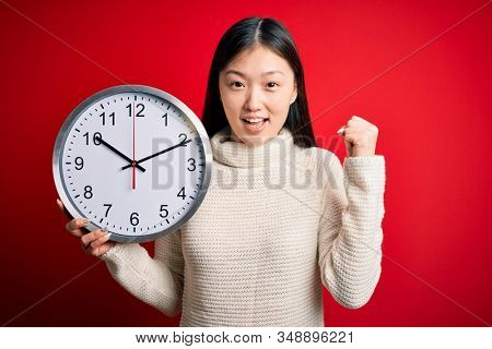 Young asian woman holding countdown big clock over red isolated background screaming proud and celebrating victory and success very excited, cheering emotion