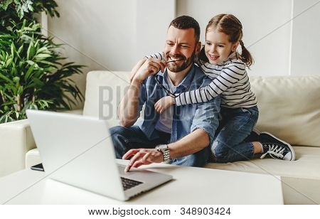 Happy Family A Businessman Father Working At Computer And His Child Daughter  At Home