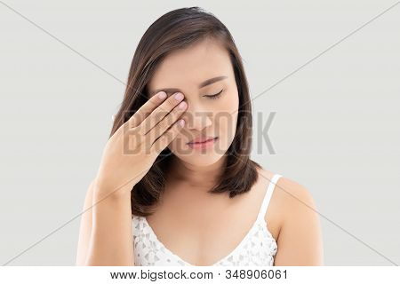 Asian Woman Suffering From Strong Eye Pain Against A Gray Background. Female Has A Pain In The Eye.
