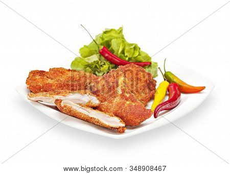 Hot Fried Crispy Chicken Fillet In Batter On A White Plate With Chilly Peppers And Lettuce. Breaded