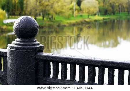 forged handrail of the bridge over the river in autumn day poster