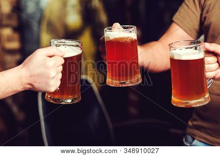Happy Friends Drinking Beer And Clinking Glasses At Pub. People, Friendship And Celebration Concept.