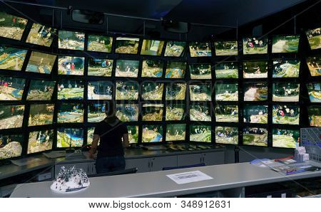 Saint Petersburg, Russia - December 9, 2019: Rear view of man looking at multiple computer screens. Monitoring system with multiple displays on the exhibition of Grand maket Russia layout