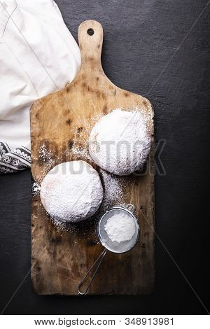 Top View Of Donuts Covered With Powdered Sugar On The Wooden Cutting Board And Stony Worktop.
