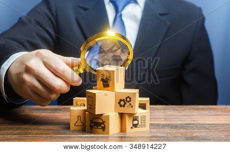 A Businessman Examines Boxes Goods With Magnifying Glass. Market Structure Research, Find Unoccupied