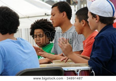 Young men drumming at music festival