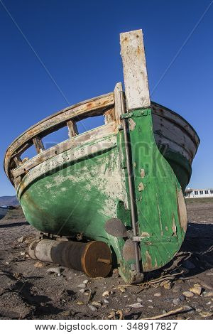 Back View Of Old Abandoned Wooden Boat On The Beach, An Old Shipwreck Boat Abandoned Stand On Beach