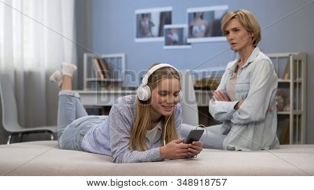 Disobedient Teenage Girl Ignoring Mother Lectures, Listening To Music On Phone