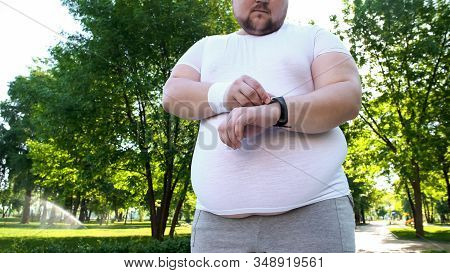 Obese Man Monitoring Heart Rate On Smartwatch After Jogging, App For Healthcare