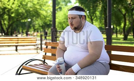 Fat Man Breathing Heavily And Drinking Amino Acids After Intense Workouts