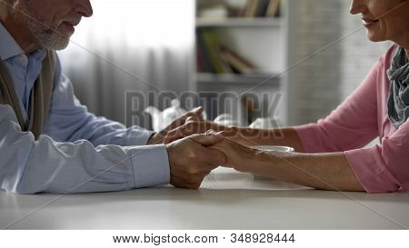 Happy Retiree Couple Holding Hands, Looking With Tenderness, Having Tea Together