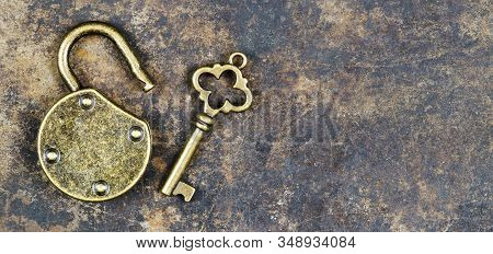 Escape room game concept. Web banner of a vintage golden key and unlocked padlock on a rusty metal background.