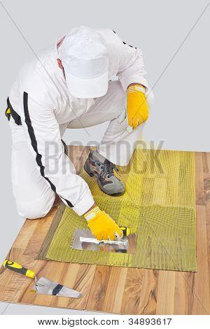 Worker Applies Tile Adhesive On Wooden Floor With Reinforcement Mesh