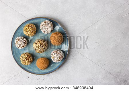Homemade Energy Balls Of Dates, Dried Apricots, Nuts And Oatmeal On A Round Plate, View From Above.