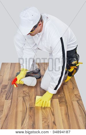 Worker Cleans With Sponge And Spray Wooden Floor Before Tilling