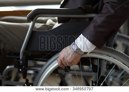 Disability Businessman With Wheelchair Against Business Office Background. Adaptation Of People With
