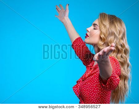 Young blonde woman with raised hands. Beautiful girl with raised arms up. Caucasian woman raising hands up. Hands up. Model in a red shirt poses in the Studio.