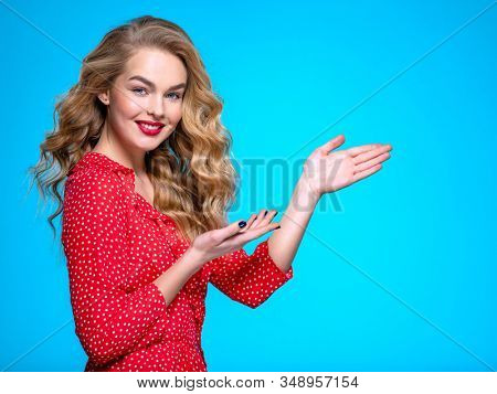Happy excited caucasian woman points on the palm. Young blonde woman with positive emotions.  Beautiful expressive girl is pointing by finger. Emotional model in a red shirt is pointing to
