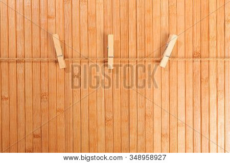 Clothespins. Wooden Clothespins On Rope Isolated On Wooden Background