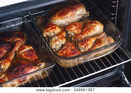 Roasted Chicken Legs And Breasts In Glass Baking Trays In An Oven. Close Up.